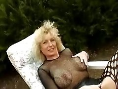 Blonde granny relaxes with dildo in nature